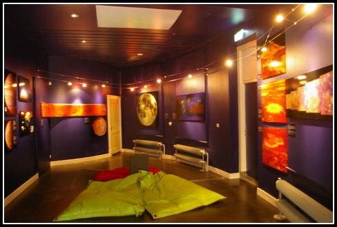 En el momento de la visita se exhibían fotos relacionadas con el Sistema Solar. En el suelo dos colchonetas verdes para ver la proyección de video sobre el techo.